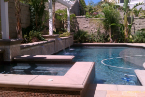 Pool with water feature and raised flower bed and pergola